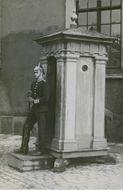 A guard standing in front of a guard house.