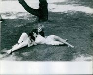 Mark Slade lays on the grassy filed with his wife Melinda Riccilli.