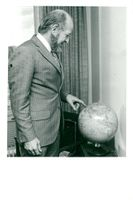 Dr. Frank Barnaby points to a globe