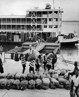 Workers carrying and putting sacks of goods on the ship.
