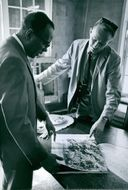 Two man watching a photo of James Meredith on news paper.