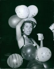 Woman standing and holding balloons, putting on head.