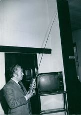 Giuseppe Zamberletti holding a radio in his hands and looking at it.