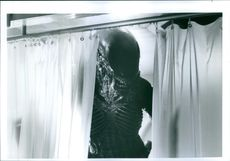 An Alien looking through the curtains during one of the scenes of the film, Alien 3.