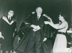 Konrad Hermann Joseph Adenauer getting honor by a woman.