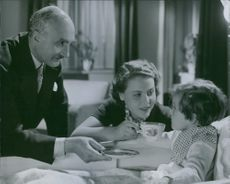 Birgit Tengroth and Kotti Chave sitting with their baby in a film Family Secret in 1936.