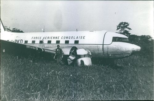 A soldier standing beside the crashed airplane in Congo. Photo taken in 1967.