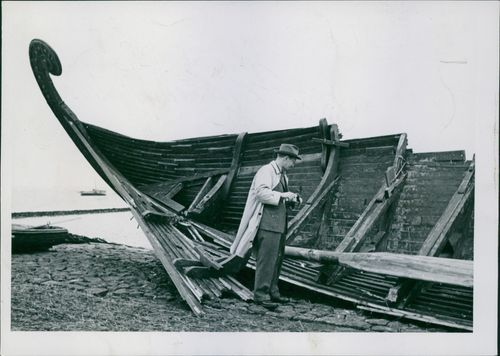 Man looking at damage boat.