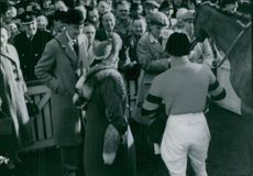 Elizabeth Angela Marguerite Bowes-Lyon with George VI standing and looking horse, while crowd gathered.