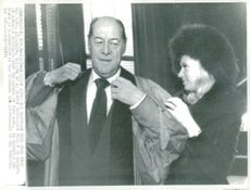 Rex Harrison from the help of his wife Elizabeth when he prepares to receive honorary doctorate at Boston University