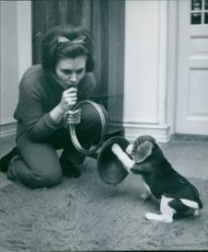 A woman blowing a brass instrument to a dog.