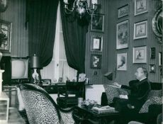 World leading fashion designer Jean is relaxing in his drawing room, he hold a cigarette