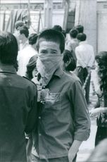 A vintage photo of a boy with a handkerchief in his face and wondering in the street of Saigon during war in Vietnam.
