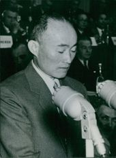 Chinese Personality Tou-Yan Tzin speaking over a microphone while the audience sits behind him.