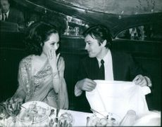 Dewi Sukarno with actor Alain Delon dining together, 1970.