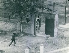 Some men are walking along a road and another one man is walking towards  a gate beside the road. 1972