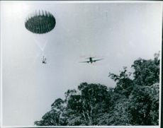 A parachute and an airplane flying on the sky.