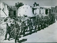 German prisoners trudge wearily through the battered streets of Medjez-el-Bab in Tunisia toward a prison camp.