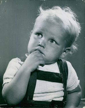 A baby curiously looking at his side, his hand rests on his chin.
