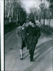 Jean-Pierre Aumont with a pipe on his mouth, walking with Marisa Pavan in a boulevard.
