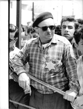 A man with a hat and sunglasses and a star on his clothe, in Israel.