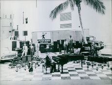 Victor Borge playing piano, other people looking at him and enjoying.