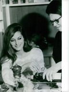 Mother of Dalida poring her a glass of wine.