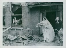 Edna Squire Brown wearing a wedding dress as she leaves her bombed home to marry Flying Officer J.C. Martin.  Taken - Circa 1945