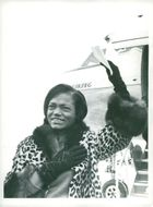 Eartha Kitt waving goodbye in his leopard hood at the airplane