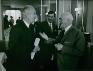 Two french socialist politician Gaston Defferre and Augustin Laurent are talking to each other and smiling