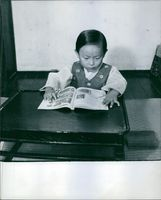 Kim Ung-yong holding a pen while reading a book. 1966.