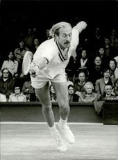 Tennis player Stan Smith throws himself behind the ball while attending Wimbledon Station.