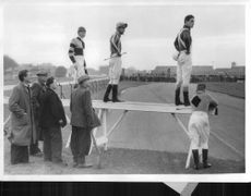 Jockeys unseated at the first fence stand on a rail to watch the rest of the race.