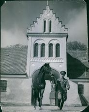 Soldier with a horse in front of a building.