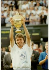 Michael Stich proudly holds his trophy after winning the Wimbledon Championship