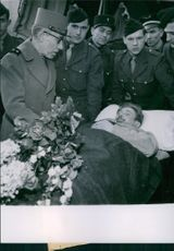 Military men gathered around a man lying in a stretcher and has flowers placed on his body.