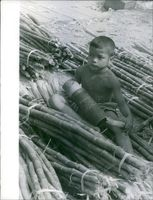 A little boy carrying a big empty shell of ammunition during Laos war.