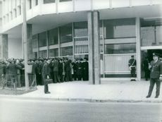 People gathered in front of building, policemen are stopping them from entering the building.