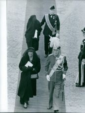 Princess Alexandra of Kent walking down the carpet with other people.