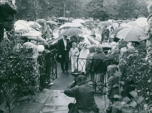 Frank Andersson on his wedding day, raining, with a man holding an umbrella and people around, watching and witnessing.