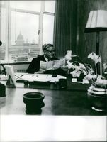Cecil Harmsworth King reading a newspaper in his office.