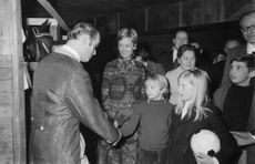 Prince Laurent shaking hand with a boy.