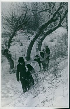 People carrying their things in the snow in Hungary during World War II.