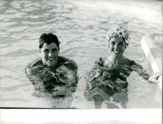Sacha Distel and his wife relaxing inside a pool.
