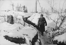 A soldier walking in middle of road.