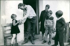Swedish actor Per Oscarsson handing over something to a child, another woman and children looking at them