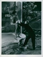 Actress Jean Simmons about to fall down, man helping her.