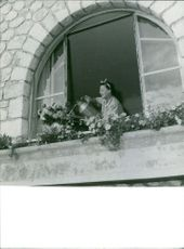 A woman giving water to the flowers in balcony.