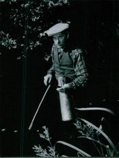 A man standing in the garden, holding stick and looking away.