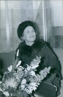A photo of a woman smiling while sitting.